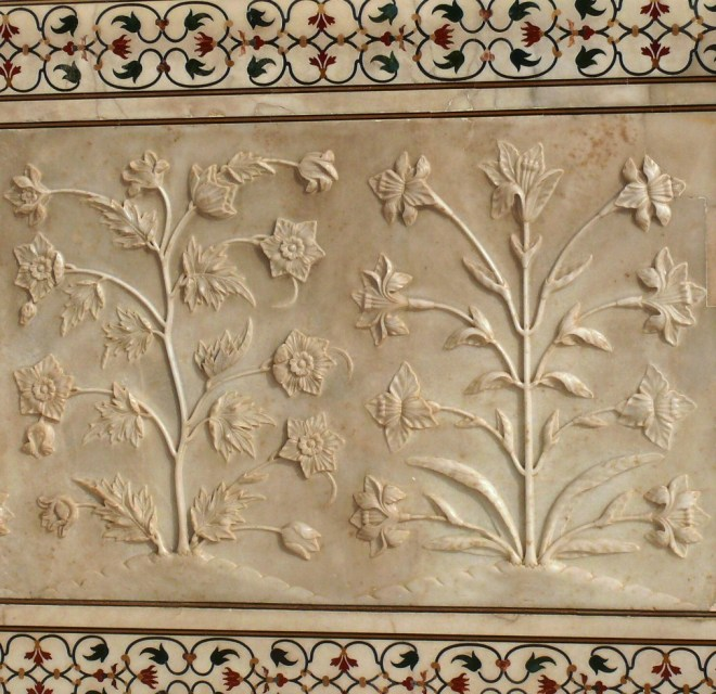 white marble dados that have been sculpted with realistic bas relief depictions of flowers and vines